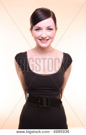 Attentive Businesswoman Smiling With Arms Behind Back