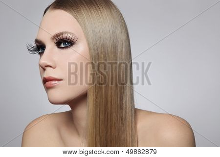 Portrait of young beautiful woman with huge fancy fake eyelashes