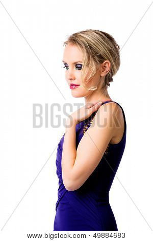 young beautiful woman with upstyle blond hair wearing tight blue evening dress on her fit slim body over white studio background. Hand on her shoulder
