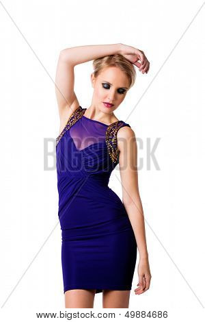 young beautiful woman with upstyle blond hair wearing tight blue evening dress with gold luxury design on her fit slim body over white studio background