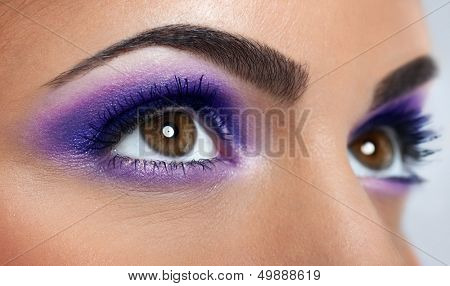 closeup of beautiful eyes with purple makeup