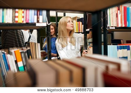 student choosing books in university library