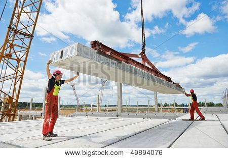 workers in safety protective equipment installing concrete floor slab panel at building construction site
