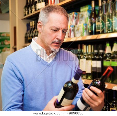 Man choosing the right wine in a supermarket