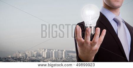 Business man holding light bulb