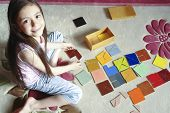 Cute little girl plays traditional  tangram / brain teaser game at home