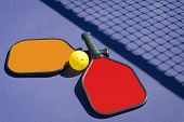 picture of pickleball  - Image of two pickleball paddles and a pickleball laying on pickleball court with net shadow - JPG