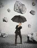 stock photo of landslide  - Businessman shelters from the storm of crisis - JPG