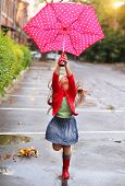 stock photo of rainy weather  - Child with polka dots umbrella wearing red rain boots jumping into a puddle - JPG