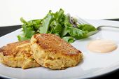 stock photo of crab-cakes  - Fresh crab cakes on a white plate with sauce and a salad of field greens - JPG