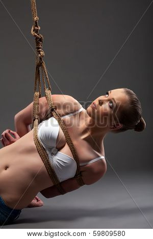 Image of pretty young woman hanging on rope