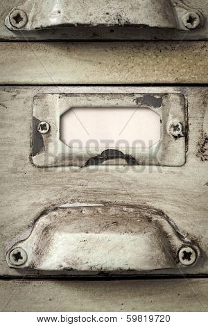 Close up of blank label in metal holder of vintage filing cabinet.  Great grunge textures.
