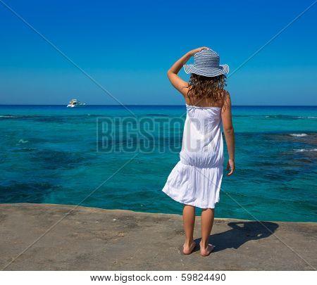 Girl rear view in Formentera Ibiza beach turquoise Mediterranean sea background