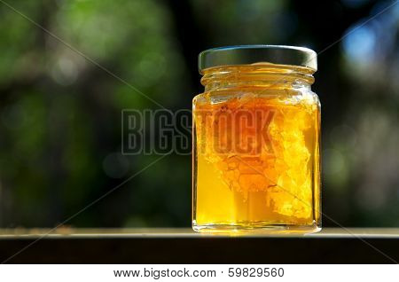 Backlit Jar Of Honey With Honeycomb On Wood