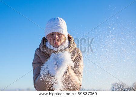 Girl blows away snow off hands