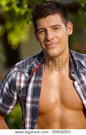 Summer portrait of handsome young man with bare chest, smiling.
