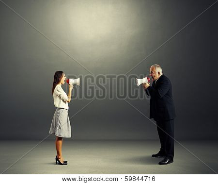 senior man and young woman screaming with megaphone in dark empty room