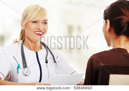 Mature female doctor talking with her patient.