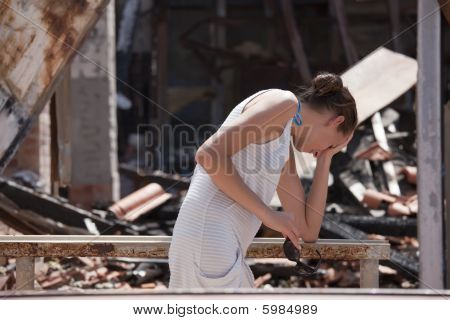 Sad Woman And Burned Out House
