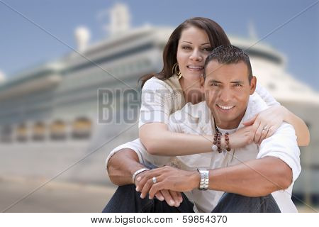 Young Happy Hispanic Couple Hugging On The Dock In Front of a Cruise Ship.