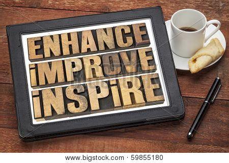 enhance, improve, inspire - a collage of motivational word in vintage letterpress wood type on a digital tablet
