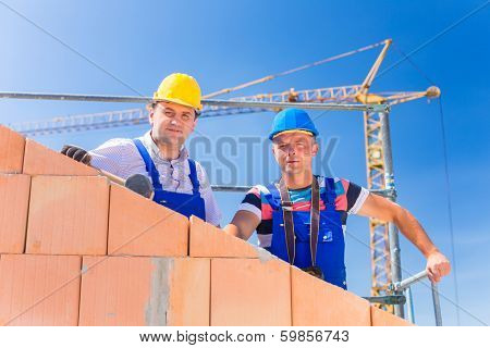 Two proud construction site workers - or bricklayers - standing on house project directing a crane with a remote control.