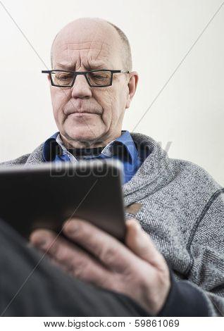 Senior man working on tablet pc