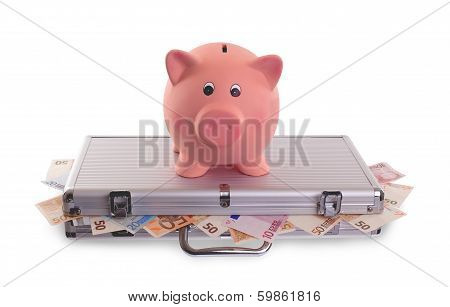 Piggy Bank On Top Of Metal Case Filled With Money