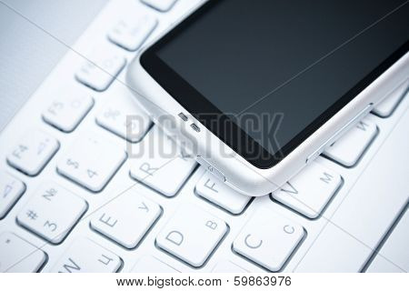 Smart Phone Over White Keyboard