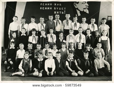 KURSK, USSR - CIRCA 1970:  An antique photo shows group  portrait of school graduates. Russian text: Lenin lived, Lenin lives, Lenin will live.