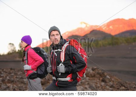 Hiking people on mountain. Hiker couple walking with backpacks outdoors in high altitude. Young man hiker in focus trekking at sunset on volcano Teide, Tenerife, Canary Islands, Spain.