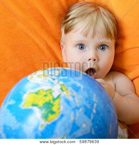 Happy baby playing with terrestrial globe on an orange plaid