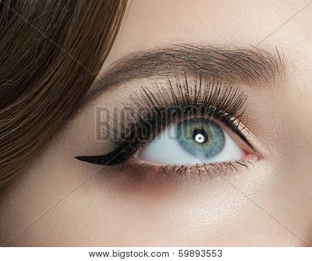 Closeup of woman eye with beautiful makeup with black eyeliner and long eyelashes