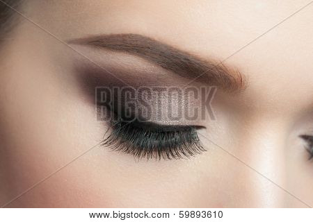 Closeup of woman eye with beautiful makeup with long eyelashes