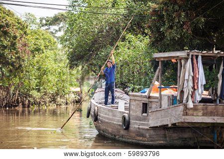 Vietnamese man rowing his houseboat
