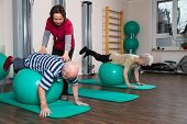 foto of supervision  - two pensioners are supervised by a physiotherapist during sports with balls - JPG