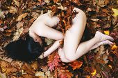 stock photo of lonely woman  - Lonely woman lying naked among autumn leaves - JPG