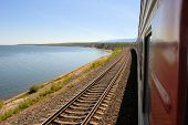 stock photo of trans  - A train of the Trans Siberian Railway is passing lake Baikal in Siberia - JPG