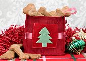 stock photo of christmas dog  - Homemade dog cookies in a decorative Christmas bag surrounded by Christmas decor - JPG