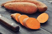 stock photo of root vegetables  - Raw sweet potatoes on wooden background closeup - JPG