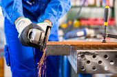 stock photo of sawing  - Craftsman sawing metal with disk grinder in workshop - JPG