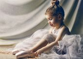 stock photo of ballet shoes  - Little girl trying on ballet shoes - JPG