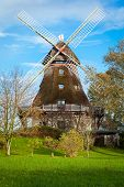 image of kinetic  - Traditional wooden windmill in a lush garden with four sails or blades turning in the wind to generate power and energy for farming or manufacture from the kinetic energy of the wind - JPG