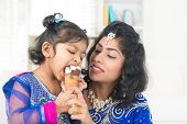 Eating ice-cream. Happy Asian India family sharing ice-cream at home. Beautiful Indian child licking