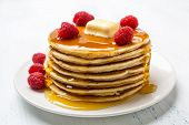 stock photo of maple syrup  - Big Pile of American  Pancakes with Raspberries - JPG