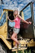 Young attractive woman on old big tractor