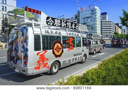 OSAKA, JAPAN - MAY 4, 2014: A caravan of a Uyoku dantai vans drives through Osaka. The right wing groups are well known for propaganda vehicles which broadcast nationalistic slogans via loudspeakers.