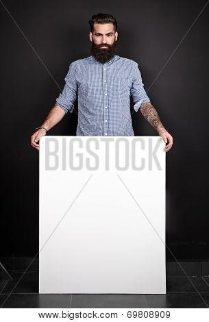 Handsome bearded man holding blank poster.