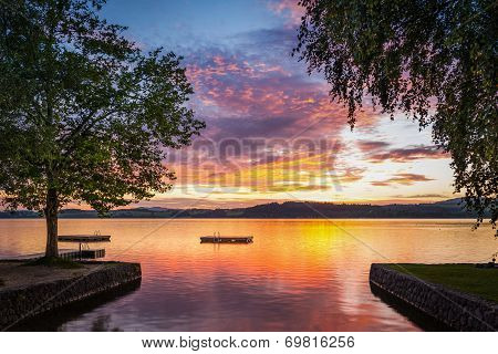 moody sunset at lake wallersee in austria with trees and wooden platform