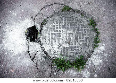 Manhole In Cracked Asphalt Surface